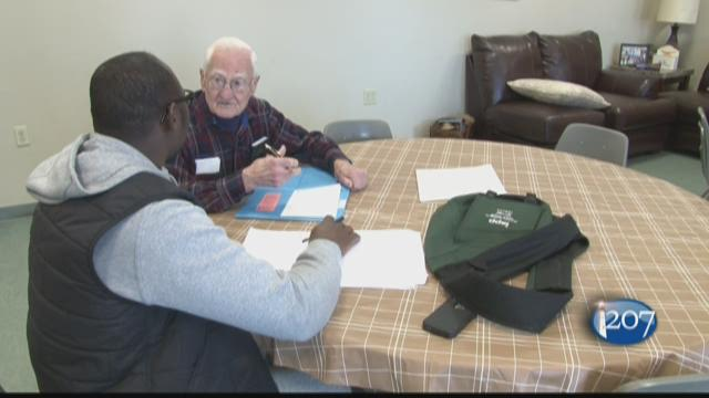 Twice a week 90-year-old Russ Hutchens helps Haroun Adam learn conversational English at the Root Cellar in Portland.
